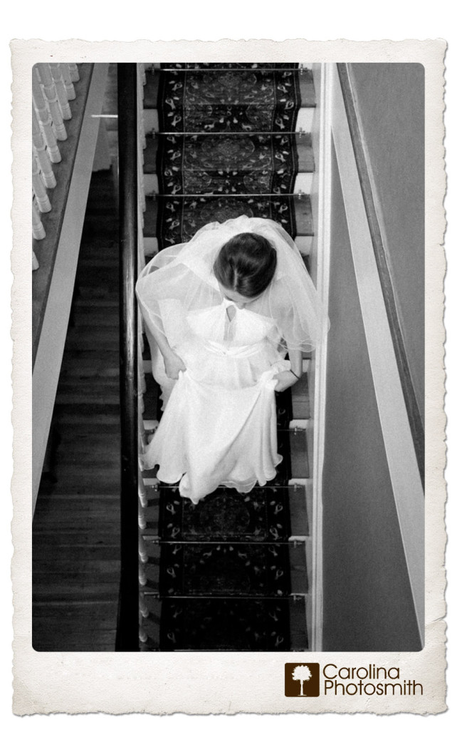 Faceless portrait of bride gracefully descending steep staircase by Carolina Photosmith