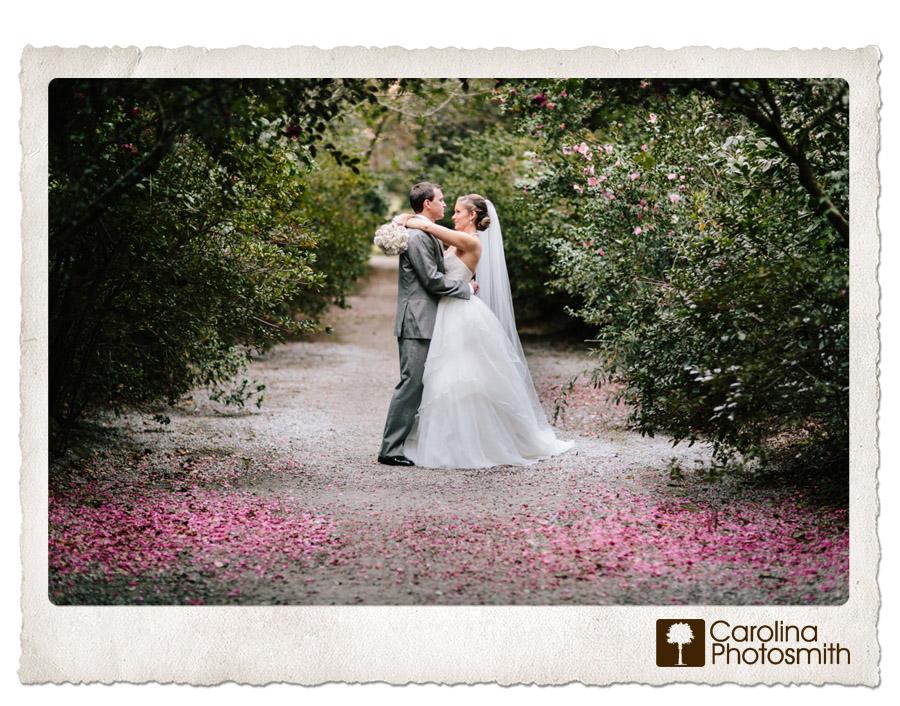 Newlyweds embrace on a pink plantation path. Vibrant outdoor wedding photography by Carolina Photosmith.