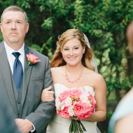 Bride on dad's arm glances at sister before walking down the aisle at Old Wide Awake Plantation. © Carolina Photosmith
