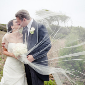 Romantic, veiled kiss on a breezy Kiawah Island wedding day. © Carolina Photosmith