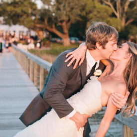 Romantic sunset kiss after Lowndes Grove wedding on the Ashley River in Charleston, SC. © Carolina Photosmith