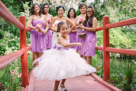 Flower girls love to twirl! Especially on a colorful bridge at Magnolia Plantation. © Carolina Photosmith