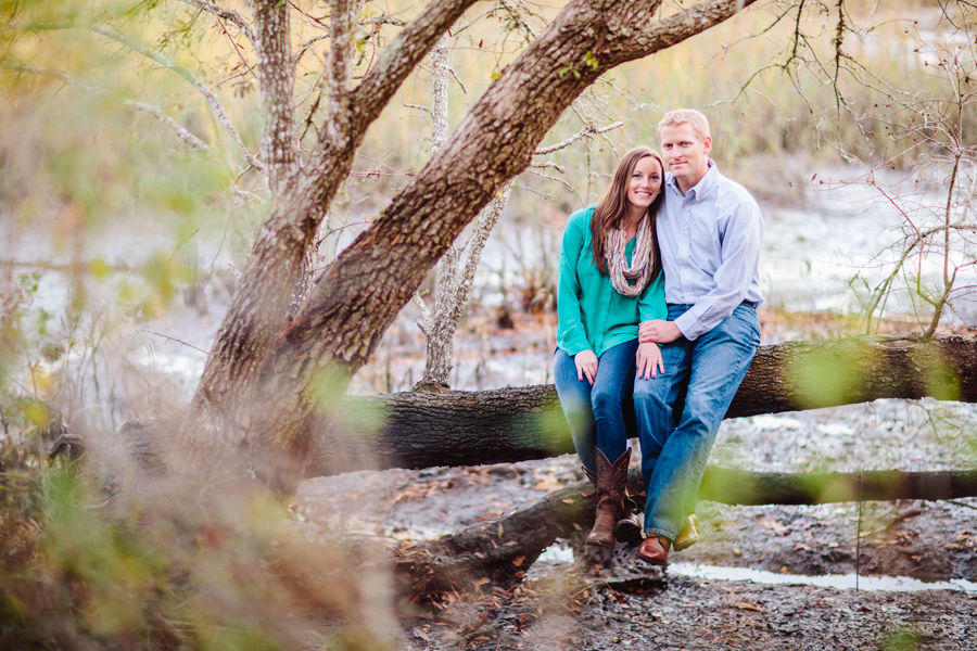 Engaged couple perches over pluff mud at their Wadmalaw Island engagement session ©Carolina Photosmith