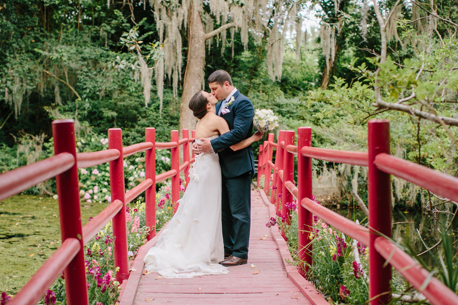 Newlyweds kiss on red bridge at Magnolia Plantation, an historic wedding venue in Charleston. © Carolina Photosmith