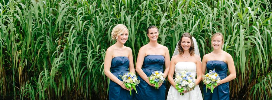 Navy bridesmaids amid lush greens at Magnolia Plantation. © Carolina Photosmith