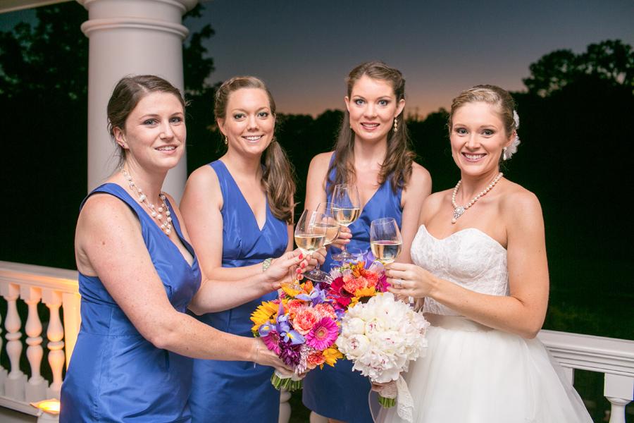 Blue bridesmaids with colorful bouquets on veranda of Magnolia Plantation house. © Carolina Photosmith