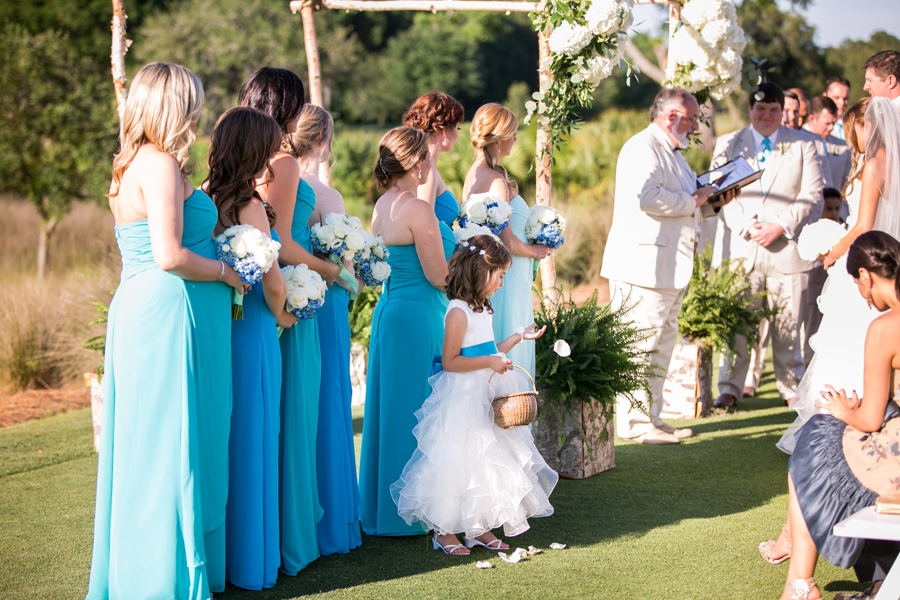 Diligent flower girl continues to toss petals during the ceremony. Awesome wedding moments. © Carolina Photosmith
