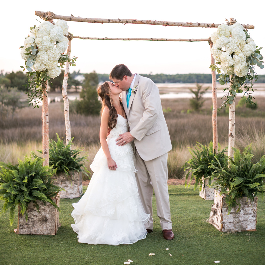 Hydrangeas and ferns adorn this marshside wedding arbor by Out of the Garden at Daniel Island Club. © Carolina Photosmith