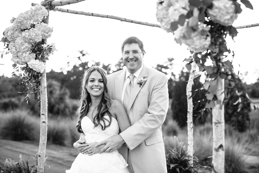 Happy newlyweds at Daniel Island Club beneath rustic wedding arbor. © Carolina Photosmith