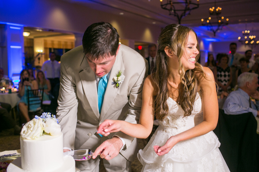 Hilarious wedding moments often ensue with cake cutting. Daniel Island Club. © Carolina Photosmith