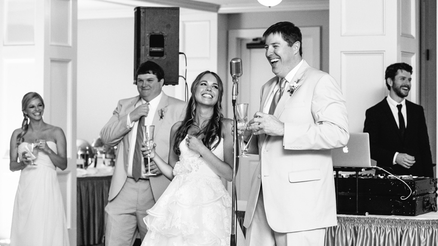 The bride adores her new husband as he toasts and makes everyone smile. © Carolina Photosmith
