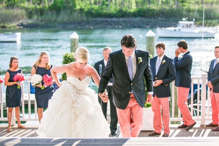 Jubilant newlyweds recess from their wedding ceremony at Kennebunk River Club. © Carolina Photosmith