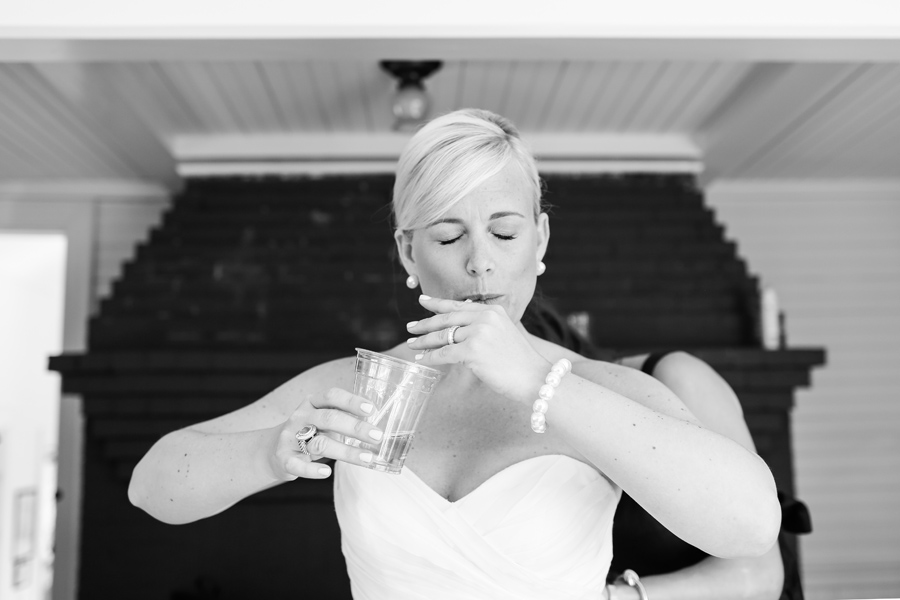 Deep breath and a touch of bubbly through a straw to relax this gorgeous bride at Kennebunk River Club. © Carolina Photosmith
