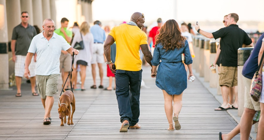 A pier walk before he gets on one knee for this historic Charleston proposal! © Carolina Photosmith