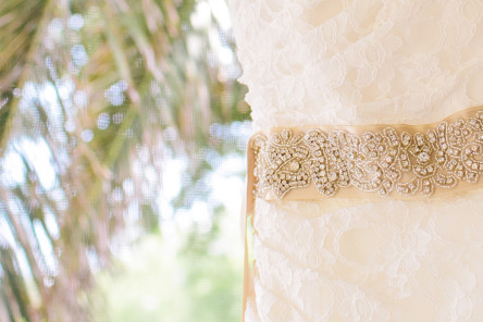 Sparkling sash on a one-shoulder gown on the screened porch of a King & Prince cottage at St. Simons Island wedding. © Carolina Photosmith