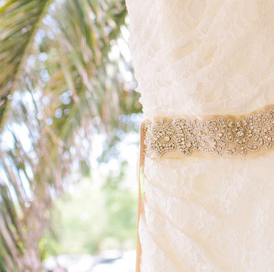Favorite wedding detail: lace, sparkling sash, palm fronds and breezy porch. St. Simons Island wedding photography by Carolina Photosmith