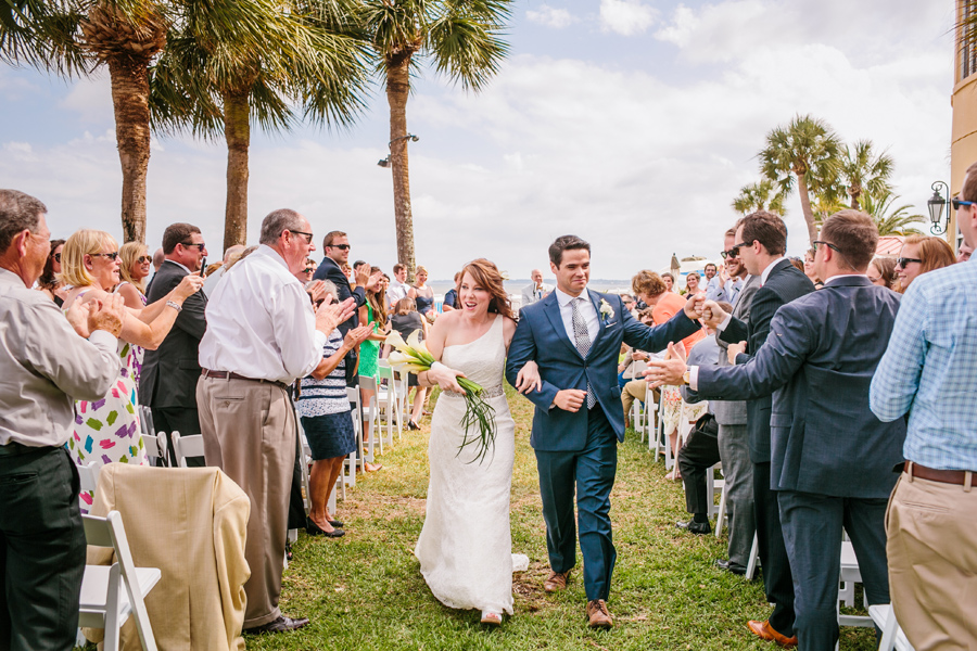 Newlyweds recess to cheers from their lawn wedding ceremony at King & Prince Resort on St. Simons. © Carolina Photosmith