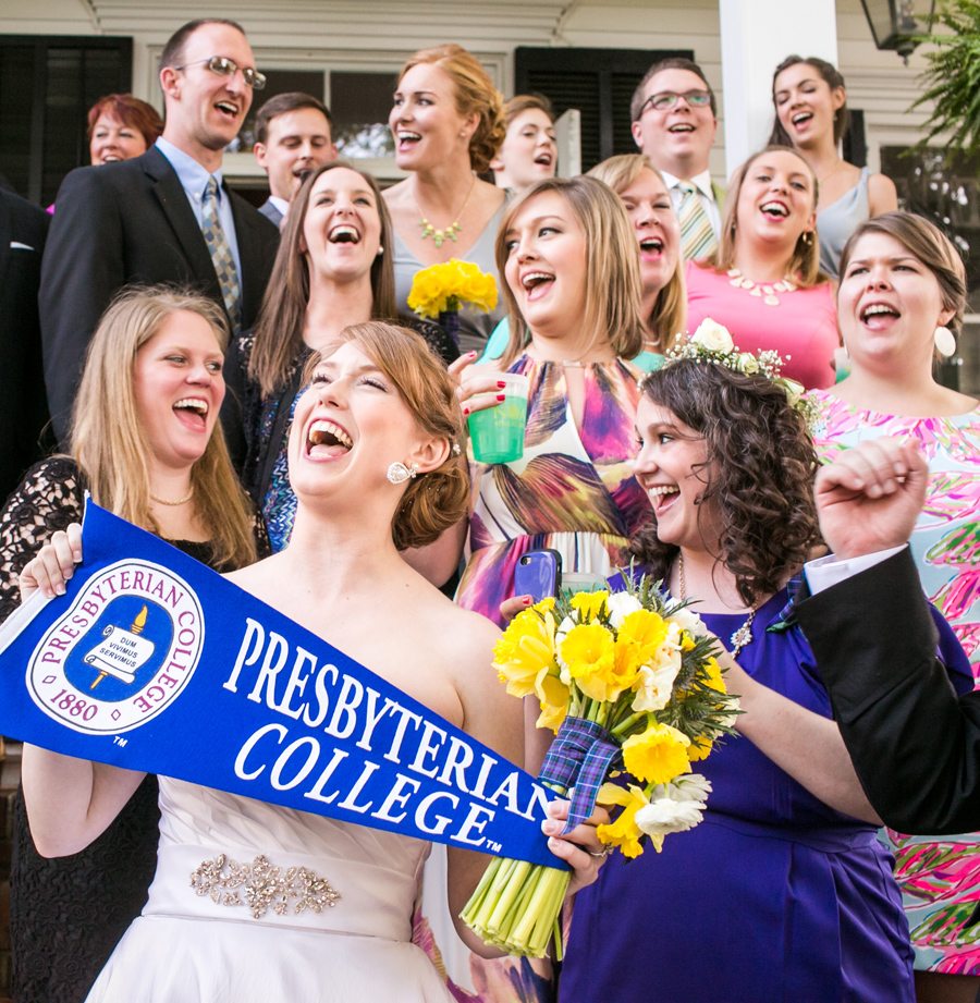 A proud PC alum croons a fight song in her wedding gown with her college mates. © Carolina Photosmith