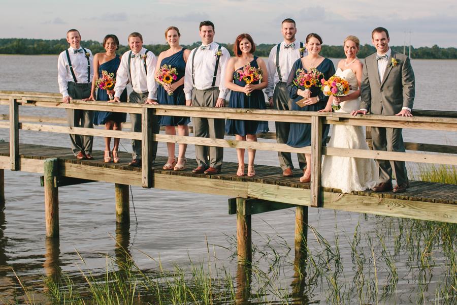 Jubilant wedding party on the dock over the Stono River at Island House wedding. ©Carolina Photosmith