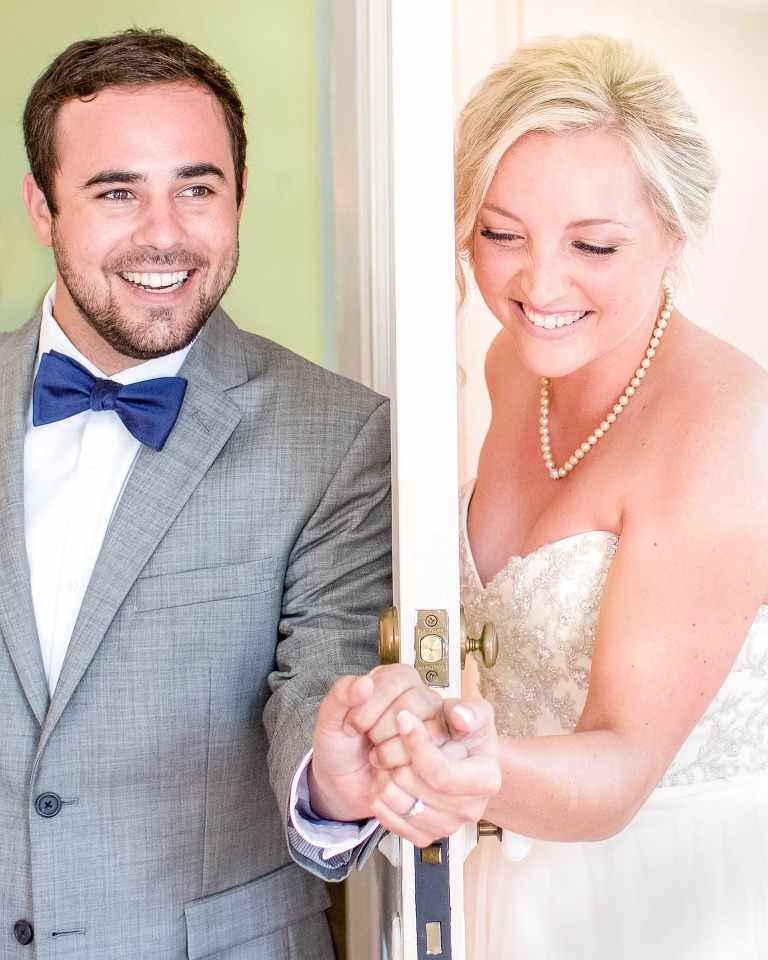 Anticipating their Lowndes Grove wedding ceremony, the almost-newlyweds hold hands around a door.
